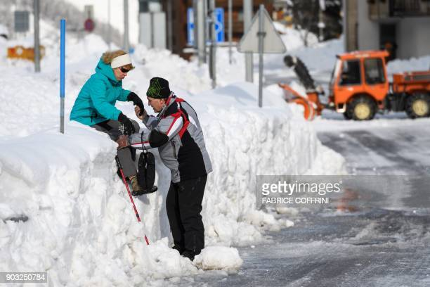 A man helps his wife to walks down a snow wall at the ski resort of Taesch on January 10 Swiss Alps Airlifts were continuing at the mountain resort...