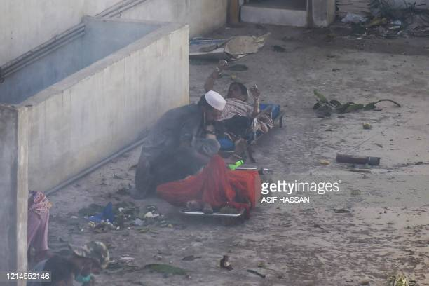 TOPSHOT A man helps injured victims after a Pakistan International Airlines flight crashed in a residential neighbourhood in Karachi on May 22 2020 A...