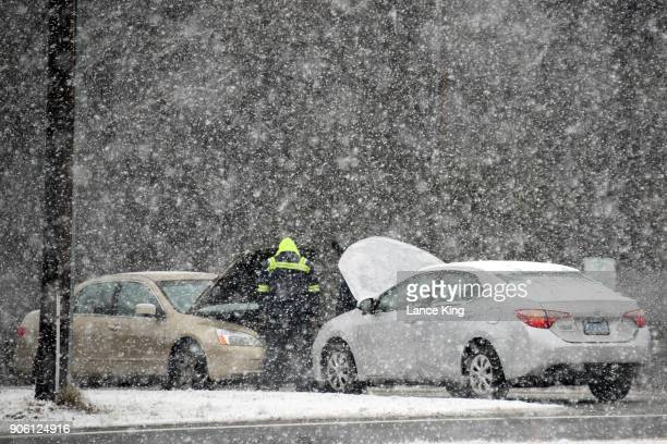 A man helps jump a car battery along New Bern Avenue as snow falls on January 17 2018 in Raleigh North Carolina Governor Roy Cooper declared a State...