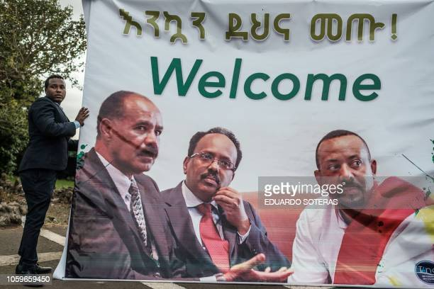 A man helps prepare the banner showing portraits of Eritrea's President Isaias Afwerki Somalia's President Mohamed Abdullahi Mohamed and Ethiopia's...