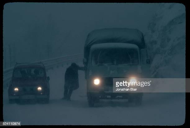 A man helps push a truck out of a snow bank in Senj Croatia Socialist Federal Republic of Yugoslavia