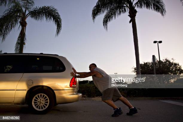 A man helps push a van which ran out of gas during the drivers nearly 5 hour wait in line toward a gas station in Estero Florida US on Tuesday Sept...