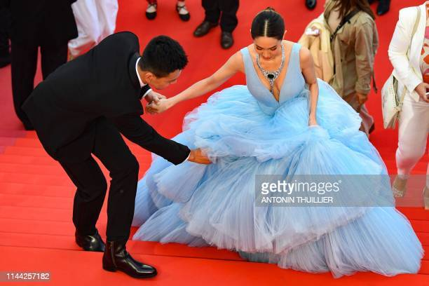 A man helps Thai actress and model Peechaya Wattanamontree with her dress as they arrive for the screening of the film Dolor Y Gloria at the 72nd...