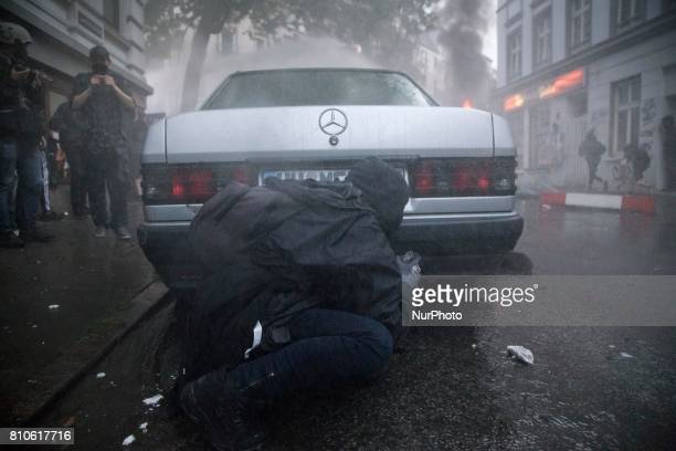 Man hides behind a car during riots in St Pauli district during G 20 summit in Hamburg on July 8 2017 Authorities are braced for largescale and...