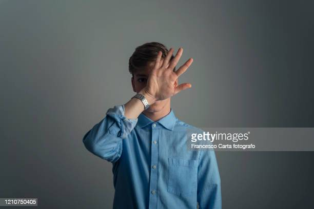 man hides behind his hand - shielding stock pictures, royalty-free photos & images