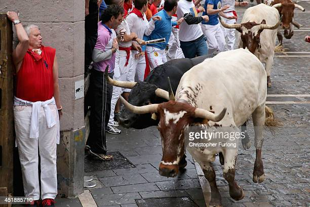 A man hides round a corner as fighting bulls from the ranch of Victoriano Del Rio Cortes run along the Curva de Estafeta during the fourth day of the...