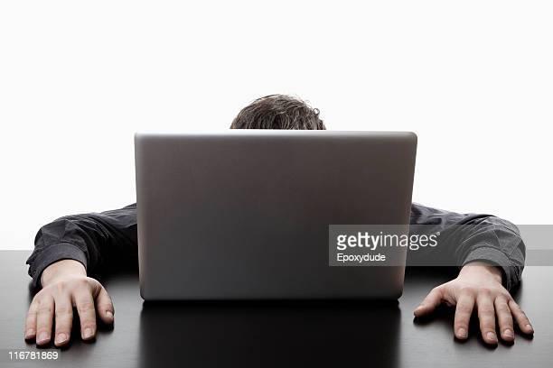A man hiding behind a laptop