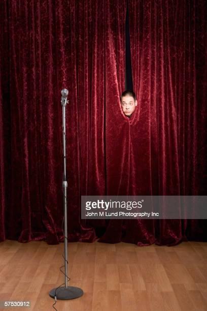 man hiding behind curtains - あがり症 ストックフォトと画像