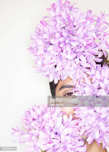 man hiding behind flowers