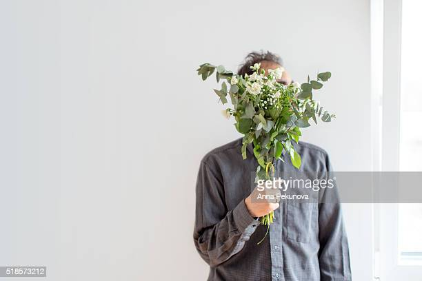 man hiding behind white roses bouquet while looking through a window - sofia rose stock photos and pictures