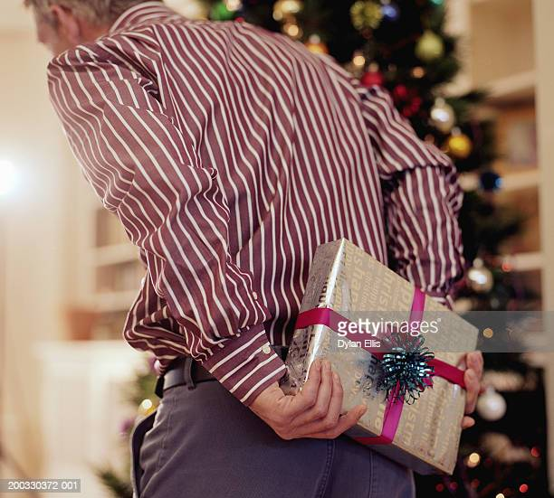 man hiding christmas present behind back, rear view - hands behind back stock pictures, royalty-free photos & images