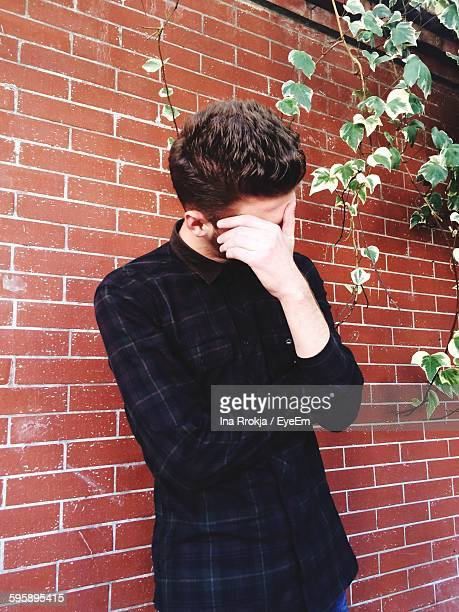 Man Hiding Face Against Brick Wall