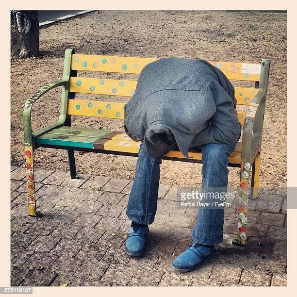 Man Hiding Face In Shirt While Sitting On Bench In Park