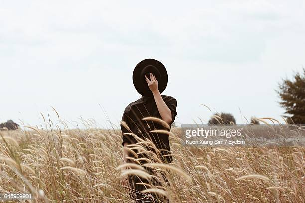 Man Hiding Face With Hat While Standing On Field Against Clear Sky
