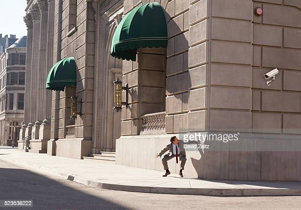 man hiding from security camera - business security camera stock pictures, royalty-free photos & images
