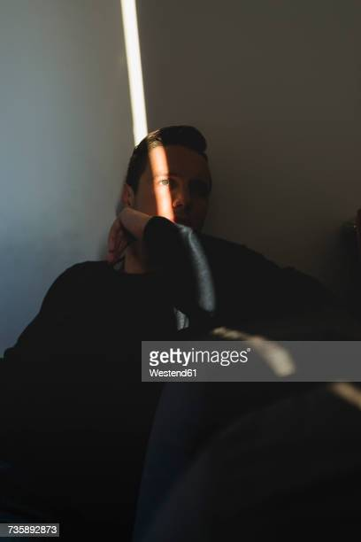 man hiding in the shadow of his room at home - one man only stock pictures, royalty-free photos & images