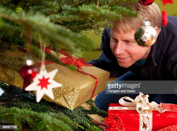 man hiding presents under christmas tree