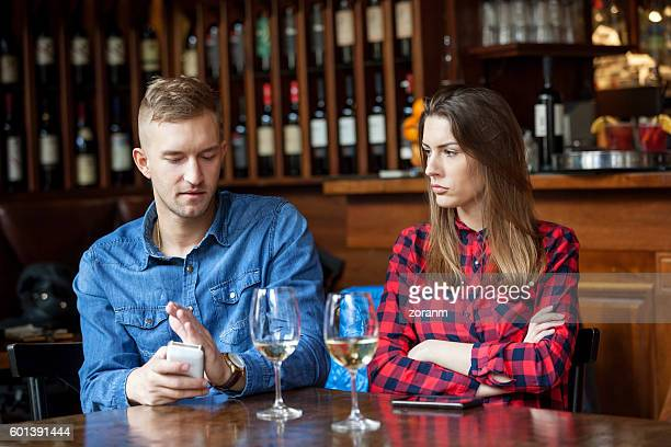 Man hiding text messages while woman is sulking