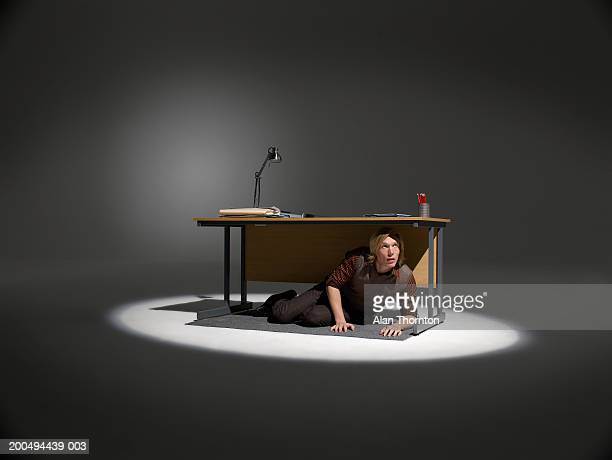 Man hiding under desk in spotlight