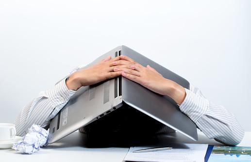 Man hiding under laptop - gettyimageskorea
