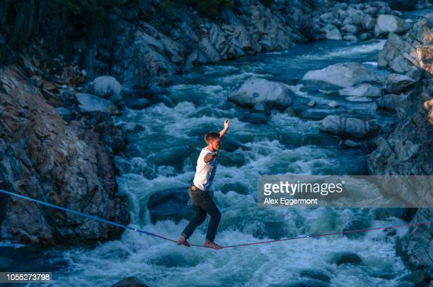 Man highlining above river, Truckee, California, USA