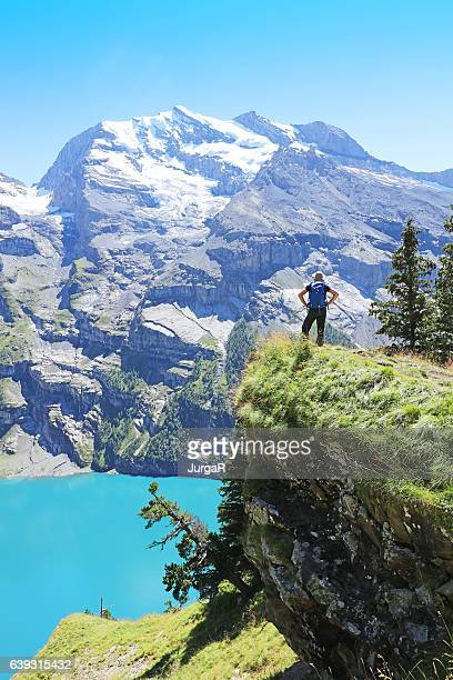 Man Hiker Looking at View over Oeschinensee Lake in Switzerland