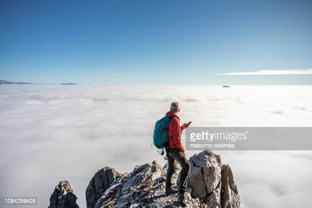 man hiker on top mountain using smart phone, blue clear sky over clouds - swiss alps stock pictures, royalty-free photos & images