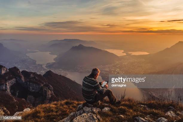 man hiker solo on the mountain during golden hour - e reader stock pictures, royalty-free photos & images