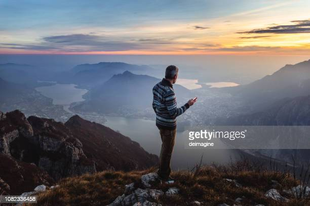 man hiker solo on the mountain during golden hour - valley stock pictures, royalty-free photos & images