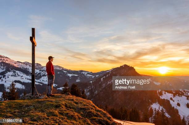 man hiker standing at summit cross enjoying beautiful sunset in the mountains - andreas solar stock pictures, royalty-free photos & images