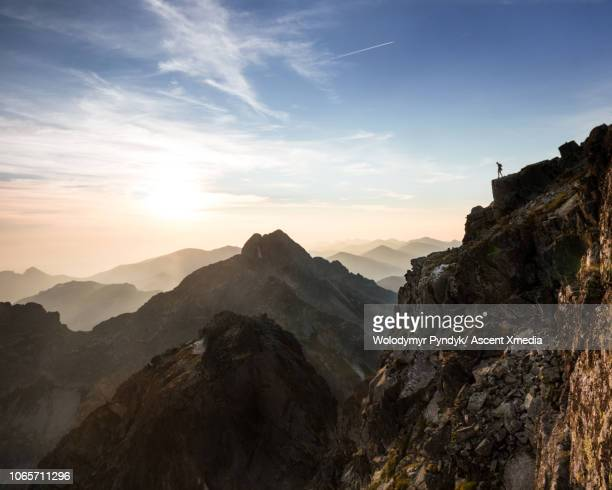 Man hiker standing on ridge and overlooking mountain valley