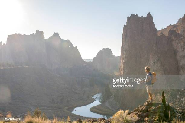 man hikes along sunny mountain ridge in the morning - smith rock state park stock pictures, royalty-free photos & images