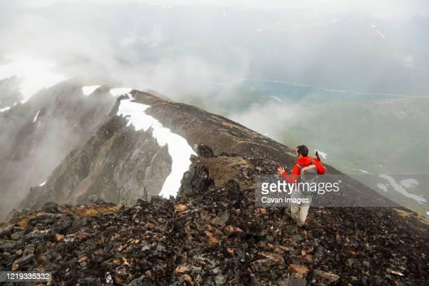 man hikes down ridge on cooper mountain, kenai peninsula, alaska - kenai mountains stock pictures, royalty-free photos & images