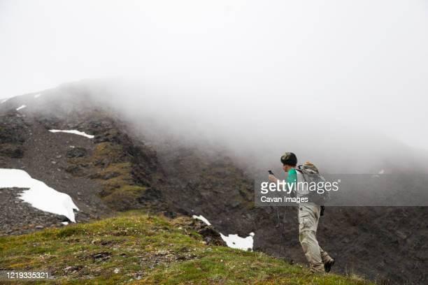 man hikes ridge towards cooper mountain, kenai peninsula, alaska - kenai mountains stock pictures, royalty-free photos & images