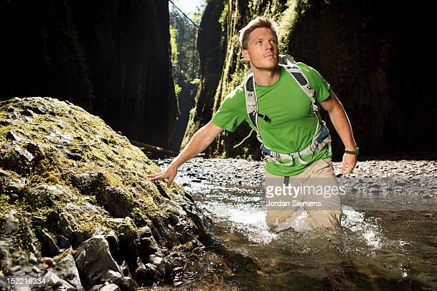 A man hiking a narrow canyon.