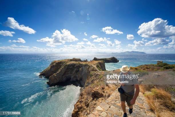 man hiking a promontory in panarea island - äolische inseln stock-fotos und bilder