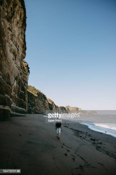Man hiking alone on beach with cliff, Chiba, Japan
