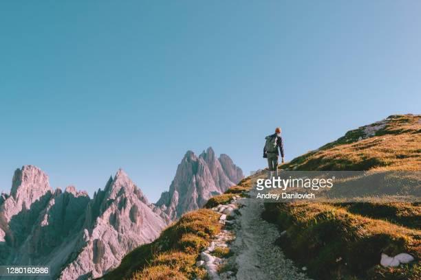 man hiking alone on the edge of the rock and looking towards the horizon. italian alps near the tre cime di lavaredo. - montanha imagens e fotografias de stock