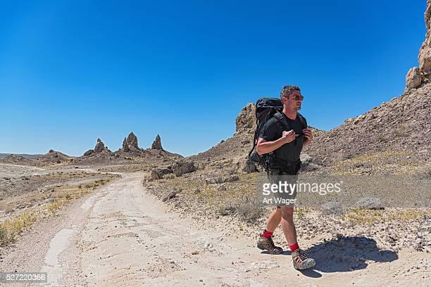 男性に沿ってハイキング、砂漠の未舗装道路