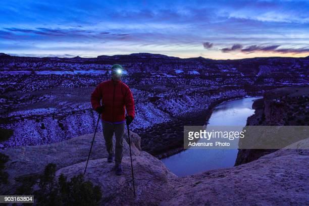 man hiking along canyon rim at night with headlamp - fruita colorado stock pictures, royalty-free photos & images