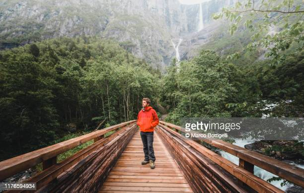 man hiking at mardalsfossen waterfall, norway - one man only stock pictures, royalty-free photos & images