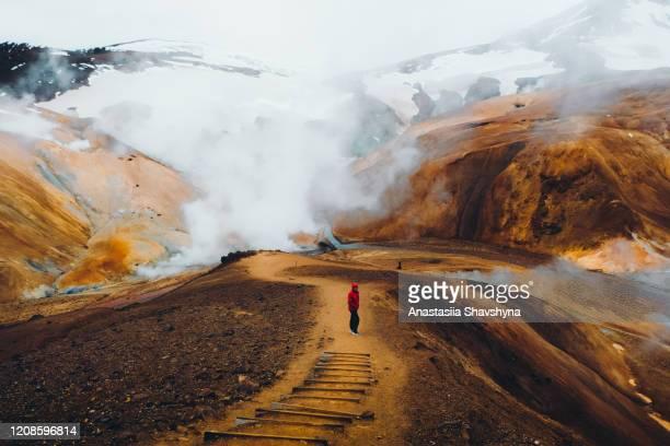 uomo che escursioni nel pittoresco paesaggio vulcanico drammatico in islanda - islanda foto e immagini stock