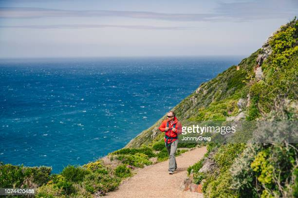man hiking by the sea - peninsula stock pictures, royalty-free photos & images