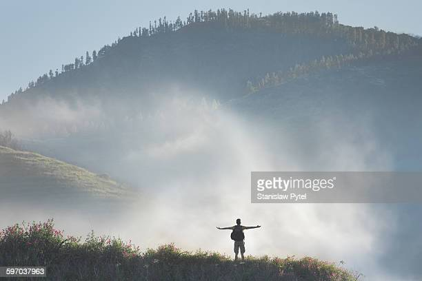 Man hiking in mountains against cloud