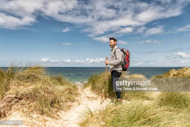 man hiking in sand dunes on the beach. - tina terras michael walter stock-fotos und bilder