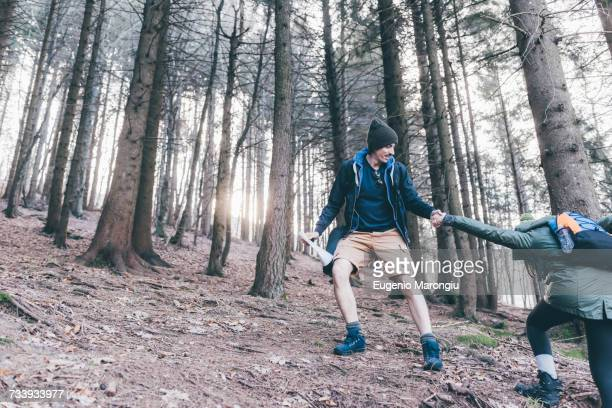 Man hiking in steep forest giving girlfriend a helping hand, Monte San Primo, Italy