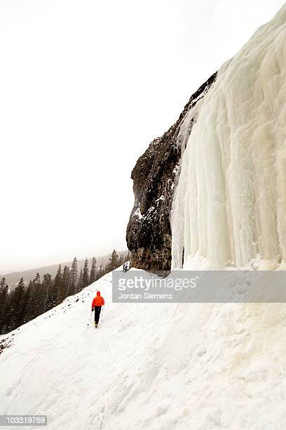 man hiking in the snow near a frozen waterfall. - bozeman stock pictures, royalty-free photos & images