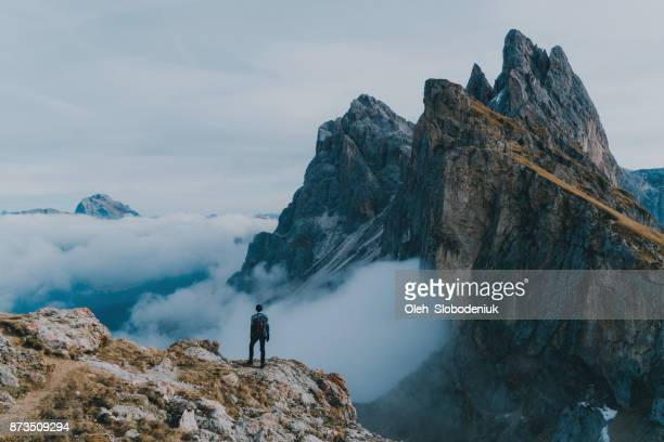 man hiking near seceda mountain in dolomites - mountain peak stock pictures, royalty-free photos & images