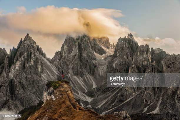 man hiking near tre cime di lavaredo with cima cadin di san lucano in background - unesco stock pictures, royalty-free photos & images
