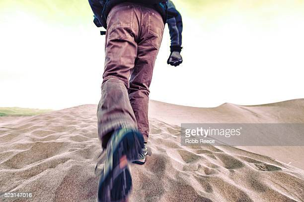 a man hiking on a sand dune in death valley - robb reece stock-fotos und bilder